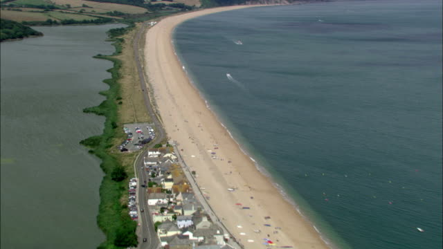 A long, narrow sandbar bisects bodies of water on the southwest coast of England. Available in HD.