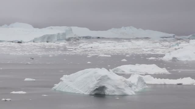 Long Panning Shot Icebergs are seen in the water off the coast of Ilulissat Greenland As the sea levels around the globe rise researchers affiliated...