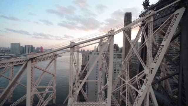 Long panning shots of the Queensboro Bridge in New York NY from a Roosevelt Island Cable Car over the East River Shots of cars during rush hour...