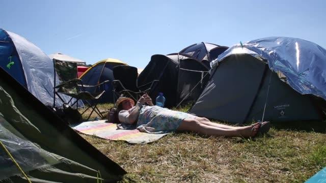 Long shot a woman texting beside tents