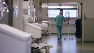 Long shot, activity in hospital operating room hallway, medical professionals walk through frame