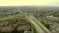 Long Shot aerial push,in , Traffic flows through a freeway interchange in a city. / California