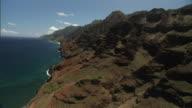 Long Shot aerial tracking-left - Rugged, unusual cliffs form Kauai, Hawaii's beautiful coastline. / Kauai, Hawaii, USA
