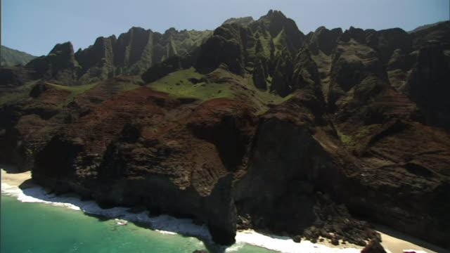 Long Shot aerial tracking-left - Waves wash against the rugged, lush coastline of Kauai, Hawaii. / Kauai, Hawaii, USA