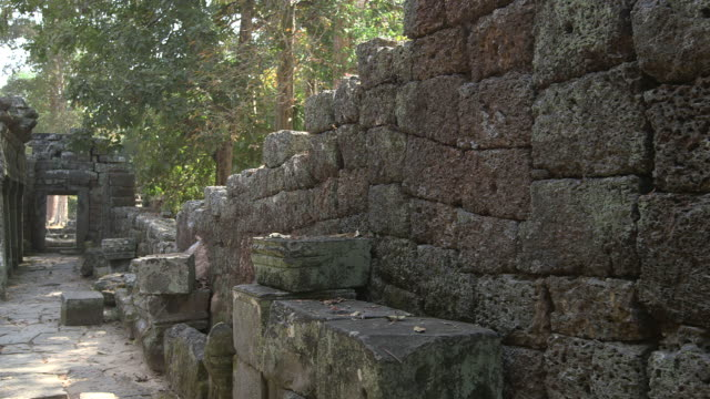 Long shot along a section of collapsed wall at the Bayon temple in Angkor, Cambodia.