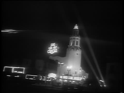 B/W 1951 long shot beams from klieg lights shining on tower of theater during movie premiere at night