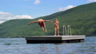 Long shot boy doing somersault off raft into lake / girl doing cannonball / Canandaigua Lake, New York