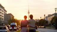 Long shot couple walking into sunset towards the Fernsehturm (TV Tower) / Berlin, Germany