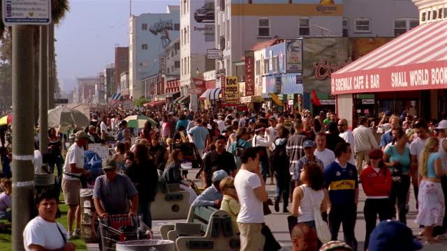 Long shot crowd walking on promenade at Venice Beach / Venice, Los Angeles, California