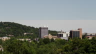 Long shot, downtown buildings protrude from the trees forming the Fayetteville AR skyline