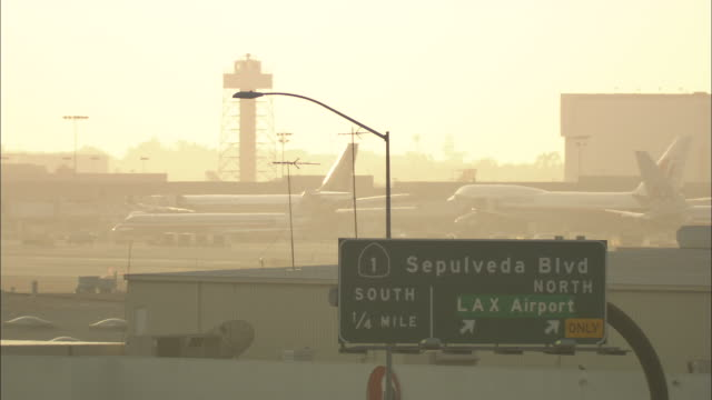 Long Shot  - Fog hangs over a sign and an airport as a passenger jet takes off