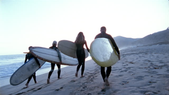 Long shot four surfers carrying surfboards along beach away from CAM with sunset in background