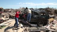 Long shot Insurance adjusters try to identify the policy holders for vehicles destroyed when a tornado ripped through the area on Monday destroying...