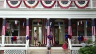 Long shot local resident Keith Chamberlin and his wife Roxanne Fulcher and their family decorate their house for July 4th celebration Takoma Park...