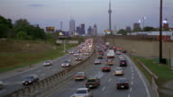 Long shot looking east over rush hour traffic on Gardiner Expressway toward Toronto skyline at twilight