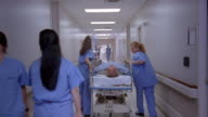 Long shot medical personnel and patients in busy hospital hallway