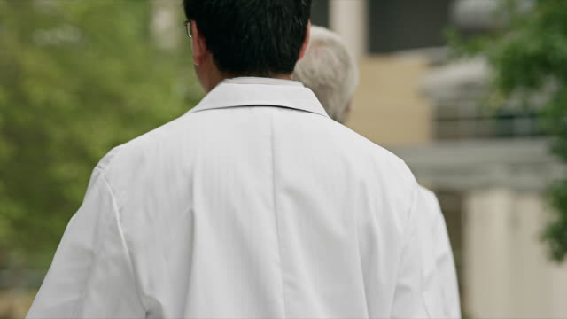 Long shot, medical professionals wearing white lab coats walk in front of modern health facility