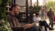 Long shot medium shot Bauhaus Books & Coffee sign / tilt down men reading in front of cafe and couples entering / Seattle