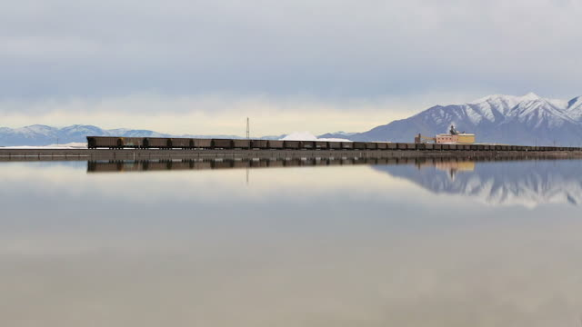 Long shot of a freight train cutting across the great salt lake in front of a salt mine