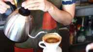 Long shot of a man pouring water into coffee filter