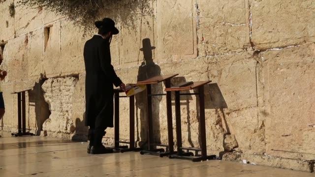 Long shot of a orthodox jew praying at the Wailing Wall