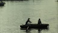 Long shot of a woman rowing across Ha Long Bay in a small boat.