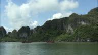 Long shot of boats travelling across Ha Long Bay, Vietnam.