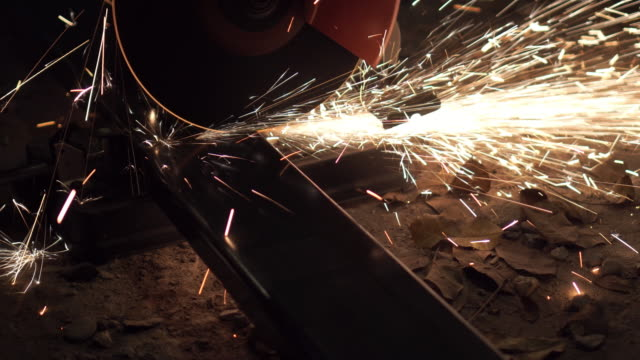Long shot of cutting metal bar by using grinder machine with sparks