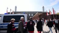 Long shot of fans walking towards stadium entrance as police van passes by 1 FC Koeln v TSV 1860 Muenchen 2 Bundesliga Editorial Video Footage at...