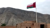 Long Shot of Flag of the Sultanate of Oman over Khasab city fortress