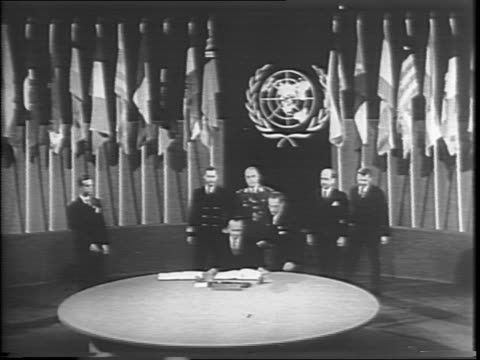 Long shot of large room with large circular table surrounded by flags / United Nations Delegates from China Russia United Kingdom France Argentina...