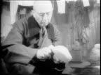 Long shot of Nazi generals in barracks / Nazi General Erich Fiedler whittling a piece of wood / General Alfred Jodl mending a sock / Wilhelm Keitel...