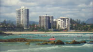 Long shot of people swimming and surfing at Surfers Paradise.