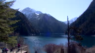 Long shot of sightseers enjoying the spectacular views in the Jiuzhaigou national park.