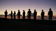Long shot of soldiers standing on the seashore with guns at dawn Australians Commemorate ANZAC Day on April 25 2013 in Various Cities Australia Long...
