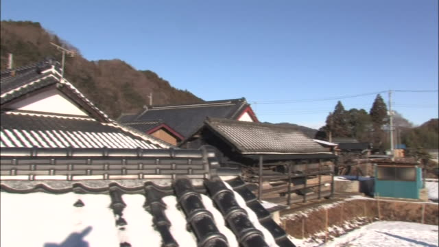 Long shot of the farm and panning right to the farmers placing konjac cake on the snow covered farm to freeze dry konjac cakes