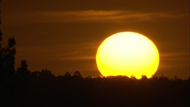 Long shot of the sun slowly setting.