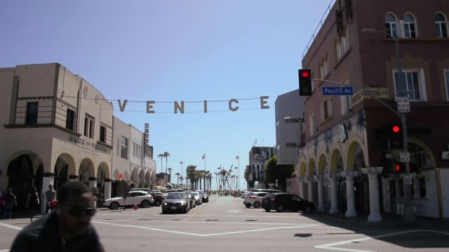 Long shot of Venice Beach street crossing with Venice Beach sign hanging over the street World renowned Venice Beach is an ocean front community best...