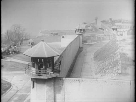 Long shot of water tower outside Sing Sing prison / shot of guard tower officer at window / shot of police and recaptured inmates in handcuffs Joseph...