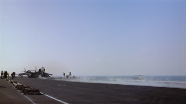 Long shot pan airplane taking off from runway on aircraft carrier / Atlantic Ocean