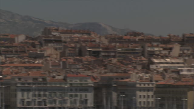 Long Shot Pan Right - Pan of the low skyline of Marseille with mountains in background / Marseille France