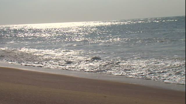 Long Shot pan-left - Sunlight reflects off the Indian Ocean near a sandy beach. / Sri Lanka