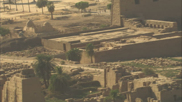 Long Shot, pan-left tracking-right zoom-out - A ruinous city faces the Nile River in Egypt