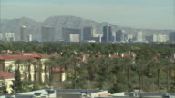 Long Shot  pan-right - The casinos on the Las Vegas Strip tower behind a suburb. /  Las Vegas