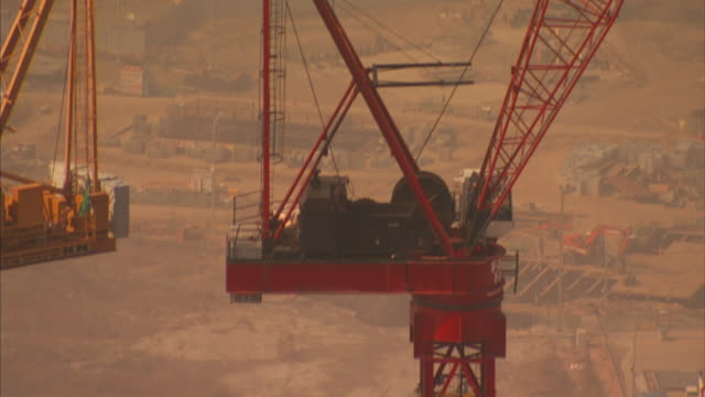 Long Shot pan-right tilt-up - A construction crew works at the base of a giant tower crane. / Republic of Korea