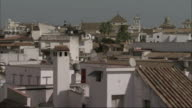 Long Shot pan-right - Whitewashed houses and tile rooftops characterize the city of Cordoba. / Cordoba, Spain