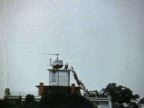 1975 long shot people climbing ladder to helicopter on roof during evacuation of Saigon / AUDIO / Vietnam