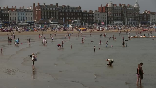 Long shot people enjoy the warm weather on the beach at Weymouth