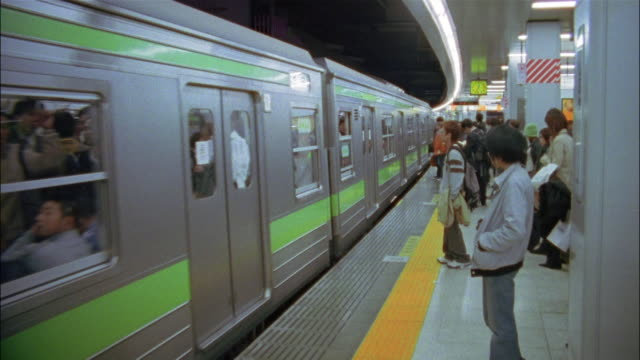Long shot people standing on platform as train arrives in station / Tokyo, Japan