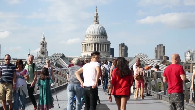 Long Shot people walking across Millennium Bridge towards St Paul's Cathedral